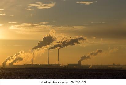Smoking chimneys power station on sunset background