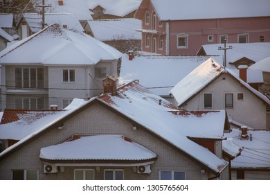 Smoking chimneys at roofs with snow of houses emits smoke, smog at sunrise, pollutants enter atmosphere. Environmental disaster. Harmful emissions, exhaust gases into air. Winter day, heating season.