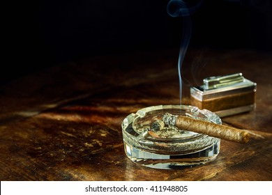 Smoking cigar sitting in round glass ashtray besides fancy lighter on wooden table
