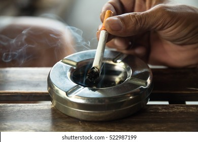 smoking a cigarette,  cigarette in hand, ashtray