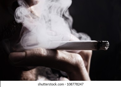 smoking cigarette in the hand of young man close up