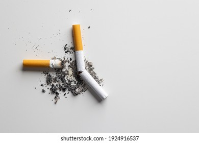 The smoking cigarette is left on the floor. Cigarette butt on the table