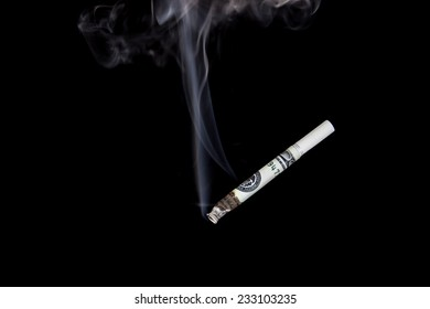 Smoking cigarette made from 100 dollar bills isolated on a black background