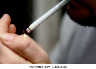 Smoking cigarette in male fingers