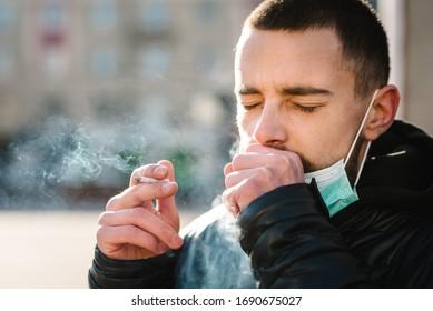 Rauchen. Nahaufnahme mit Maske während COVID-19 Pandemie Husten und Rauchen einer Zigarette auf der Straße. Rauchen verursacht Lungenkrebs und andere Krankheiten. Die Gefahren des Rauchens.Coronavirus.