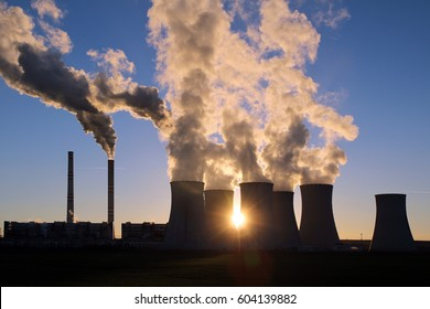 smoking cooling towers of coal power plant against the sun