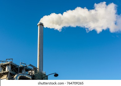 Smoking factory chimney. The tall metallic smokestack of an incineration plant is spitting out a long cloud of thick white smoke against blue sky.