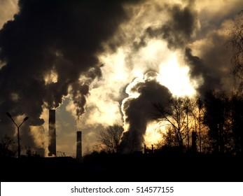 Smoking factory chimneys in morning backlighted by rising sun