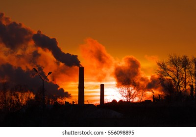 Smoking factory chimneys in morning backlit by rising sun