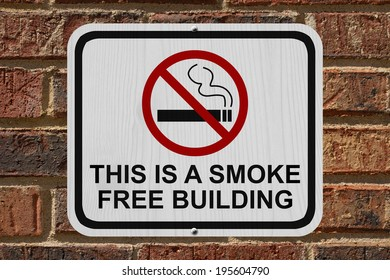 Smoking Free Building Sign, An red and white sign with cigarette icon and not symbol with text on a brick building