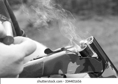 Smoking gun concept,  black & white of a double barreled over/under shotgun immediately after firing with shallow depth of field focused on the smoke leaving the breech