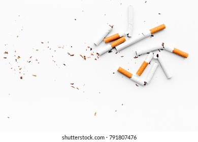 Smoking. Half-smoked cigarettes with ash on white background top view copy space