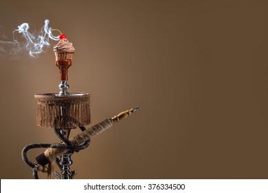 Smoking hookah with chocolate muffin head on dark background