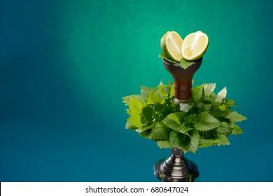 Smoking hookah with fruit head on dark background