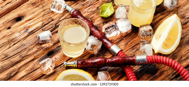 Smoking hookah and glasses with alcoholic limoncello.Oriental nargile