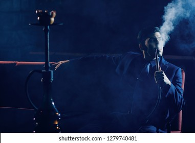 Smoking hookah shisha, young man is resting in nightclub, dark background, white cloud of smoke.