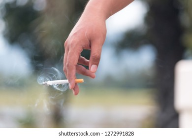 Smoking in human hands with blurred background smoke