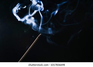 smoking incense sticks on a black background
