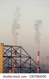 Smoking from industrial chimneys of heating plant emits smoke, smog at sunset in city, pollutants enter atmosphere. Environmental disaster. Harmful emissions, exhaust gases into air. Heating season.