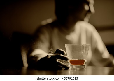 Smoking man with a glass of whiskey and cigar