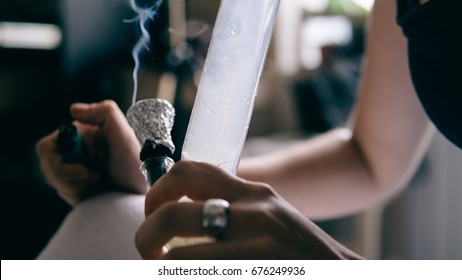 Smoking marijuana with a bong close-up .