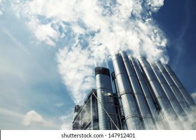 Smoking metal chimneys against blue sky