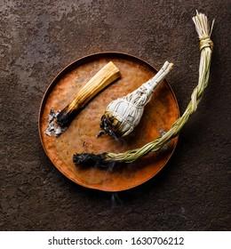 Smoking organic herbal Incense Palo santo stick, White sage and Sweet grass on dark background
