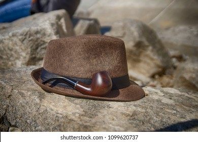 Smoking pipe and man hat lying on the rock. HDR image