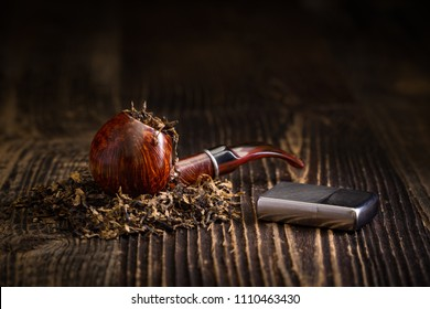 Smoking pipe with tobacco leaves on a rustic wooden table