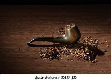 Smoking pipe tobacco on dark background