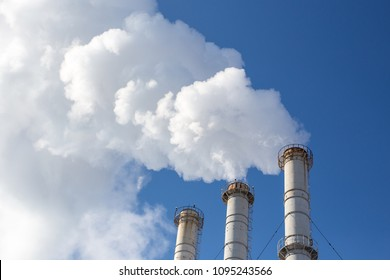 Smoking pipes making clouds against blue sky background. Dioxide air contamination. Environmental pollution