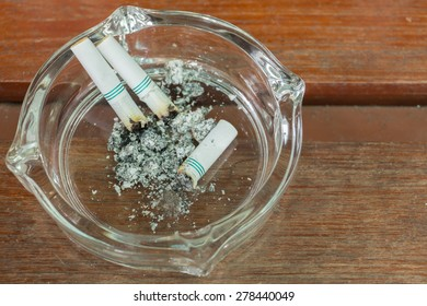 Smoking and then placed in an ashtray.on wood background