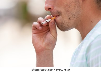 Smoking problem, addiction to nicotine concept. Adult man in light shirt smoking cigarette outside.