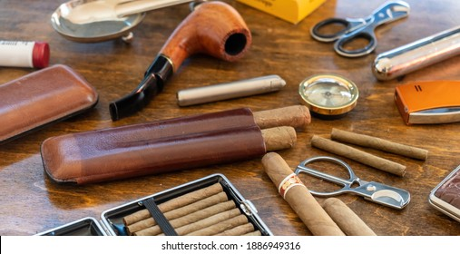 Smoking set accessories. Cigars, pipe, cigarillos and cigarettes, cutters, lighters, cases on a wooden table background. Cuban quality brand cigars, luxury lifestyle closeup view - Shutterstock ID 1886949316