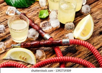 Smoking shisha and glasses with alcoholic limoncello.Hookah and alcohol