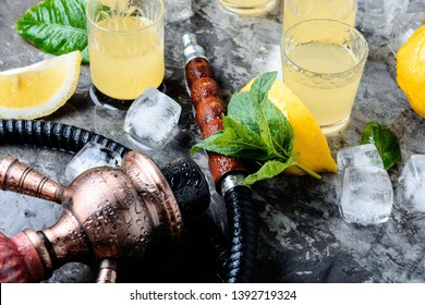 Smoking shisha and glasses with alcoholic limoncello.Hookah and alcohol