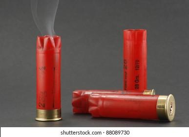 smoking shotgun cartridges on a grey background
