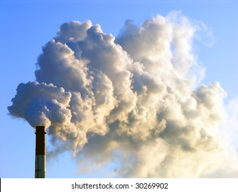 Smoking stack of thermal power station against a blue sky