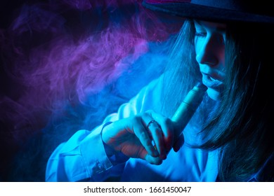 Smoking steam. Young girl with a vape device. A woman smokes an electronic cigarette. Vaper in the clouds of steam. The concept is a less harmful alternative to smoking. Vaper in the dark