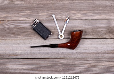 Smoking tobacco pipe and pipe smoking accessories (lighter and tamper) on wooden background. Top view.