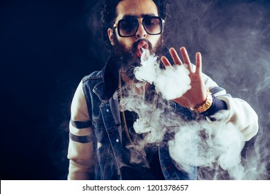 Smoking vape. vaping man holding a mod. Vape Rings. A man launches a ring of smoke. Tricks with smoke.