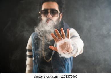 Smoking vape. vaping man holding a mod. Vape Rings. A man launches a ring of smoke. Tricks with smoke.