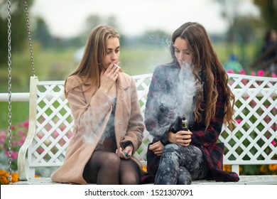Smoking and vaping. Young beautiful white teeage girls in casual clothes sit on a vintage bench and smoke and vape cigarettes on the street in the evening. Electronic cigarette. Bad habit.