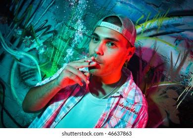 Smoking young man against graffiti wall background.