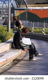 Smoking young man reading a brochure (searching for a job or for a flat) sitting on a bench in a city.
