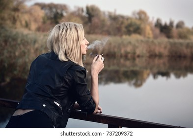 Smoking young woman. Girl with cigarette standing on the bridge.