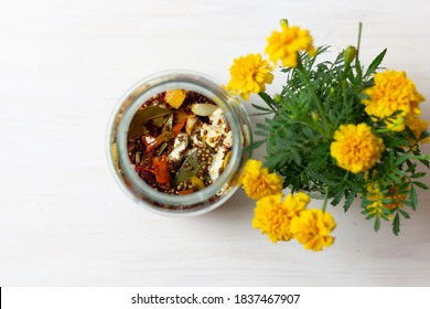 Smoky Marinated Feta in olive oil with spices in glass jar and marigold flowers top view