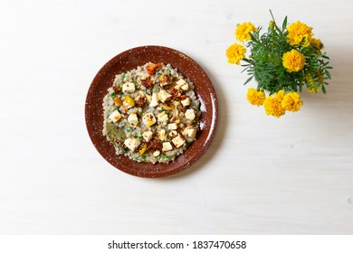 Smoky Marinated Feta in olive oil with spices and green buckwheat on brown plate an marigold flowers