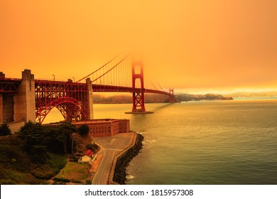 Smoky orange sky on Golden Gate Bridge of San Francisco skyline from Fort point. Californian fires in United States of America. Composition about wildfires and climate change concept.