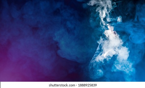 Smoky VAPE background. Vaper in a cloud of smoke. A man in a top hat and glasses smokes VAPE. Space for text. VAPE shop. E-cigarette smoker on a dark background.